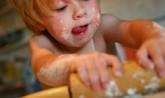 Toddler boy helping bake in kitchen